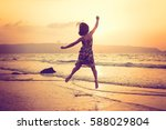 happy girl jumping at the beach ... | Shutterstock . vector #588029804