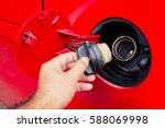 Small photo of Close up shot of a car's. Open fuel tank lid in red car. Refueling a car at a fuel station.