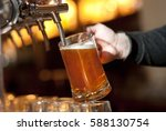 beer is poured into a glass | Shutterstock . vector #588130754