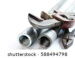 Small photo of pipe alligator wrench, pliers and steel pipes on white background