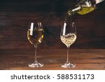 two glasses pouring white wine... | Shutterstock . vector #588531173