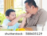 asian child feeding father with ... | Shutterstock . vector #588605129
