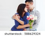 Small photo of portrait of happy couple, husband and wife with spring flower bouquet