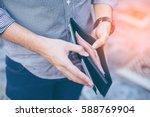 Stock photo man standing holding black wallet full of money 588769904