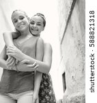 Small photo of Black and white portrait of student friends girls hugging, joyful smiling looking, in picturesque city street on school trip holiday, outdoors. Adolescent women travel lifestyle together, exterior.