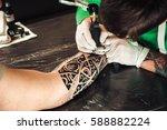 master tattoo artist in gloves... | Shutterstock . vector #588882224