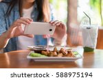 hands of woman taking a photo... | Shutterstock . vector #588975194