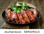 roasted pork ribs in frying pan | Shutterstock . vector #589039613