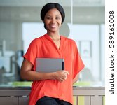 Small photo of Square portrait of black entrepreneur holding a digital tablet while smiling happily at the camera wearing a bright orange shirt while standing in her usual business environment.
