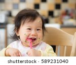 baby eating messy mashed potato | Shutterstock . vector #589231040