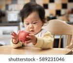cute baby girl eating apple on... | Shutterstock . vector #589231046