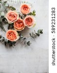 Stock photo orange roses and decorative branches on white textured backgroun 589231283