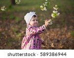 Small photo of Beautiful little girl with admiration considers flowering branch on the spring background. Soft focus