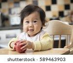 cute baby girl eating apple on... | Shutterstock . vector #589463903
