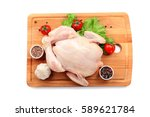 Small photo of Cutting board with whole raw chicken and vegetables on white background