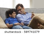 smiling father and son sitting...   Shutterstock . vector #589741079
