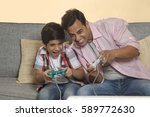 father and son sitting on sofa... | Shutterstock . vector #589772630