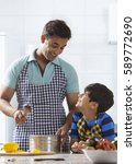 father and son cooking in... | Shutterstock . vector #589772690