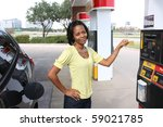 Pretty woman at gas station using credit card paying for gas - stock photo