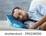 handsome depressed man lying on ... | Shutterstock . vector #590238500