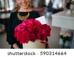 Stock photo the girl in a black blouse holds a gift in the hands of a rich bouquet of red roses the 590314664