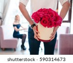 Stock photo man holding gift bouquet of red roses for woman composition of flowers in white hatbox 590314673