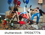 Small photo of Messy room after wild house party, three tipsy stylish friends relaxing on couch while blond-haired woman with teddy bear posing for photography