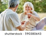 happy senior couple playing... | Shutterstock . vector #590380643