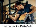 handsome man doing biceps... | Shutterstock . vector #590448686