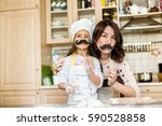 mother and daughter cooking | Shutterstock . vector #590528858