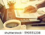 Small photo of Businessman or CEO or CFO seriously analyses a company financial reports on his table. Financial reports are set of documents prepared by an administrative team at the end of an accounting period.