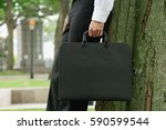 businessman leaning on tree ... | Shutterstock . vector #590599544