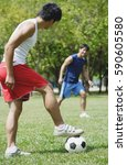 two men playing soccer in park | Shutterstock . vector #590605580