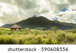 small plane flying over huts in ... | Shutterstock . vector #590608556