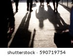 Small photo of Blurry silhouettes and shadows of people walking on the city sidewalk