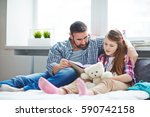 Small photo of Full-length portrait of pretty family: little girl holding teddy bear in hands while reading adventure story to her bearded middle-aged father