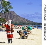 Small photo of WAIKIKI BEACH, HONOLULU, HAWAII - SEPTEMBER 16, 2012: Santa Claus with fiddle waves aloha and wishes everyone on Waikiki Beach an early Merry Christmas.