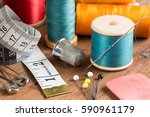 Small photo of Spools of thread and basic sewing tools including pins, needle, a thimble, and tape measure on a wooden tabletop