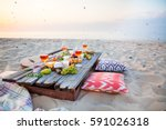 picnic on the beach at sunset... | Shutterstock . vector #591026318