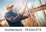 young fisherman angling on the... | Shutterstock . vector #591061574