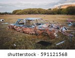 Small photo of abbandoned rusted jalopy in the middle of a field, USA