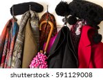 Small photo of Colorful clothing, coats, hats and umbrella on coat hook – cold winter season