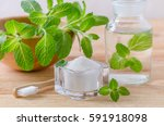 Small photo of alternative natural mouthwash bottle with toothpaste xylitol, soda, salt, and wood toothbrush closeup, mint on wooden background