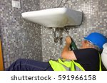 plumber at work with a sink | Shutterstock . vector #591966158