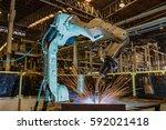 robot is welding steel part in... | Shutterstock . vector #592021418