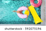 woman relaxing on donut lilo in ... | Shutterstock . vector #592075196
