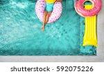 woman relaxing on donut lilo in ...   Shutterstock . vector #592075226
