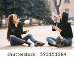 Two Young Adult Girls Sitting...