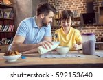 father and son preparing... | Shutterstock . vector #592153640