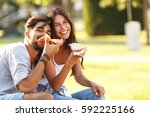 young couple sitting on park... | Shutterstock . vector #592225166